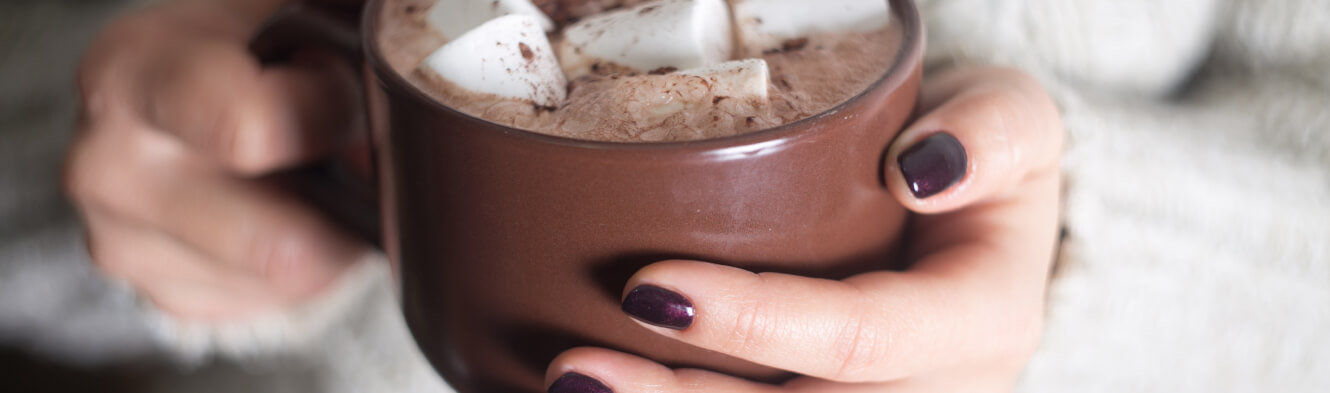 Hands holding a mug of hot cocoa
